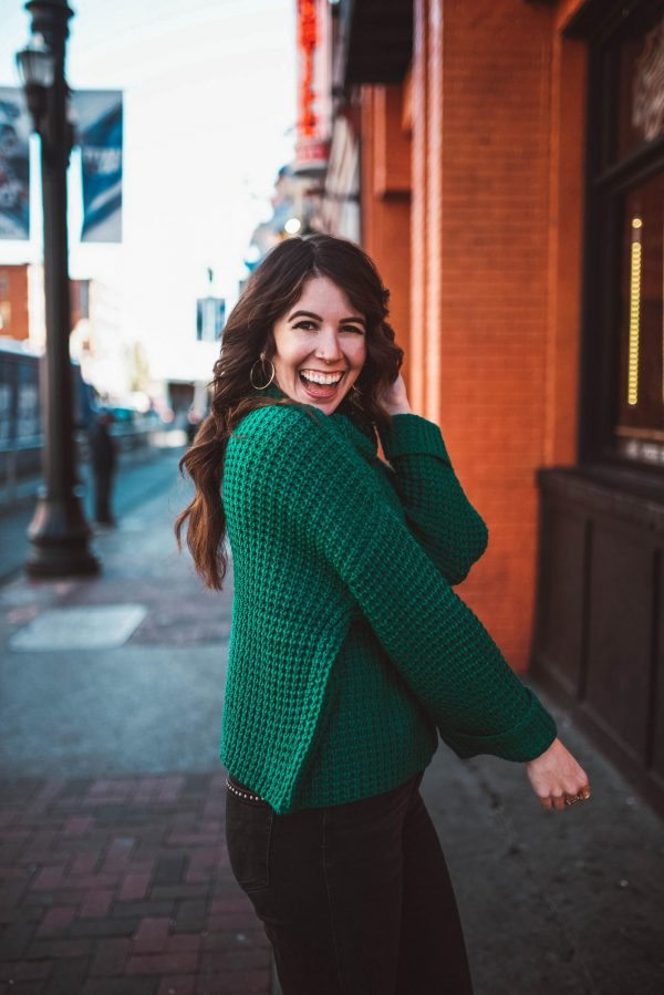 All the Free Stuff To Get On Your Birthday by popular life and style blogger, Greta Hollar: image of a woman dancing outside and wearing a green knit sweater and black jeans.