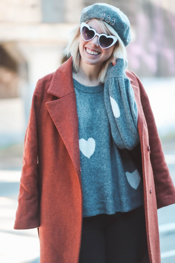 5 Cute Valentine's Day Looks that Aren't Dresses | Greta Hollar |Valentine's Day Looks by popular Nashville tall fashion blogger, Greta Hollar: image of Greta Hollar wearing a  grey and white heart print sweater with a grey beret and red wool jacket.