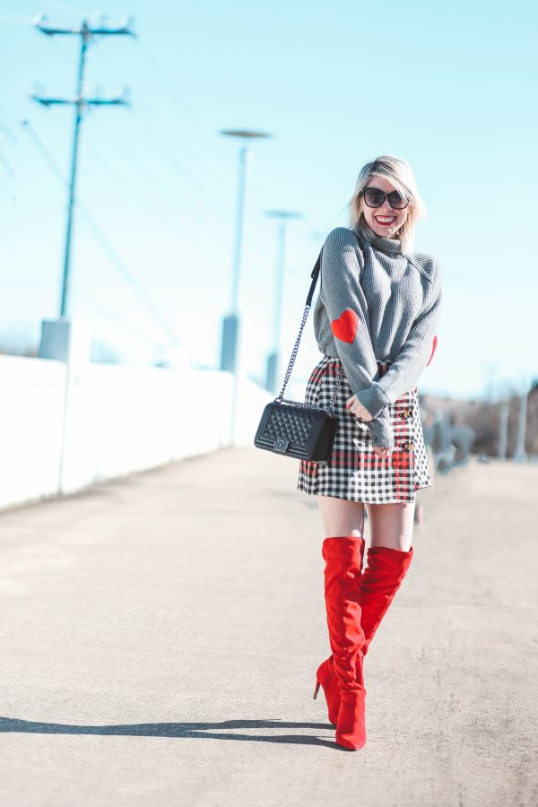 Cute Heart Sweaters featured by top US fashion blogger Greta Hollar; Image of a woman wearing Chicwish sweater, Steve Madden boots, Target skirt, Amazon handbag and Target sunglasses.