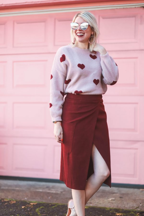 Cute Heart Sweaters featured by top US fashion blogger Greta Hollar; Image of a woman wearing ASOS skirt, Chicwish sweater, Target shoes and Kendra Scott earrings.