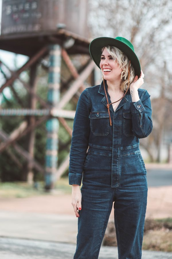 Cute Winter Looks featured by top US fashion blogger Greta Hollar; Image of a woman wearing Madewell jumpsuit, Urban Outfitters hat, Steve Madden shoes and Target earrings.