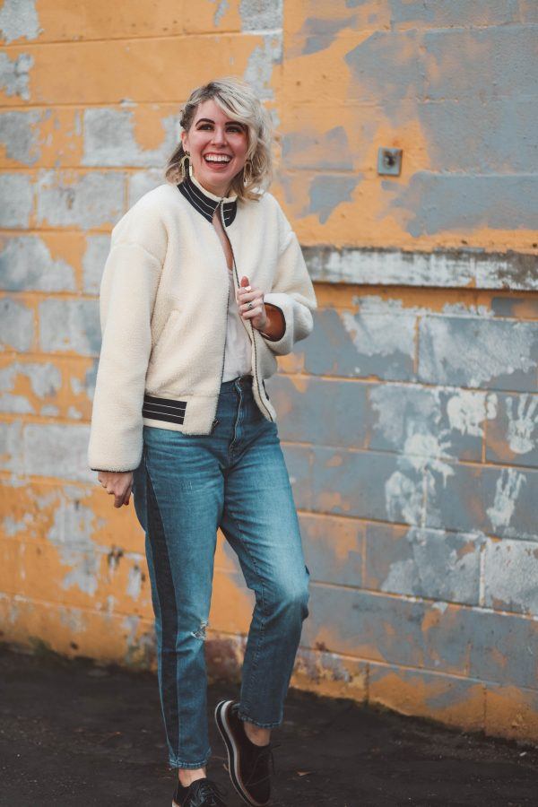 Cute Winter Looks featured by top US fashion blogger Greta Hollar; Image of a woman wearing Madewell jacket, Madewell jeans, Free People bodysuit, Halogen shoes and Target earrings.