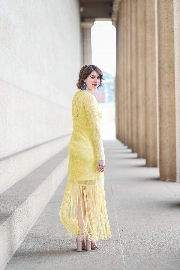 Hair Care Routine featured by top US beauty blogger Greta Hollar; Image of a woman wearing a yellow spring dress and nude heels.