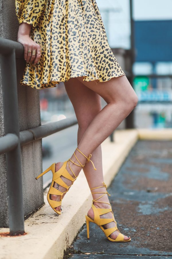 Spring Wedding Guest Dress featured by top US fashion blogger Greta Hollar; Image of a woman wearing leopard print Anthropologie dress, dupe Gucci belt, Ego shoes and Urban Outfitters sunglasses.