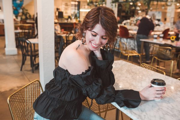 Black Off the Shoulder Top featured by top US fashion blogger Greta Hollar; Image of a woman wearing ASOS black top, jeans and Adidas.