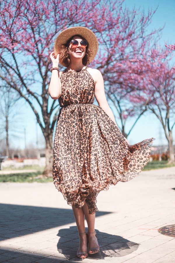 Travel Essentials for Women featured by top US travel blogger Greta Hollar; Image of a woman wearing Chicwish leopard dress, Steve Madden shoes, ASOS hat and Target sunnies.