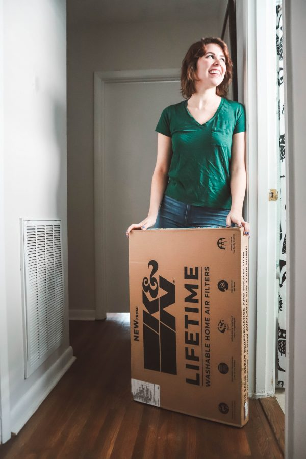 How to Get Your Home Ready for Spring featured by top US lifestyle blogger Greta Hollar; Image of a woman changing an air filter.