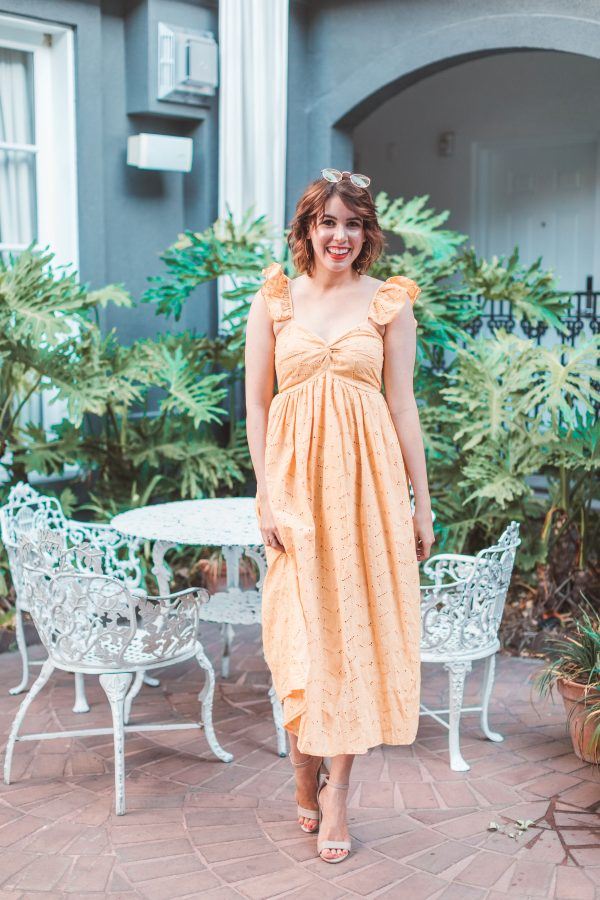 Kimpton Brice Hotel featured by top US travel blogger Greta Hollar; Image of a woman wearing a yellow dress.