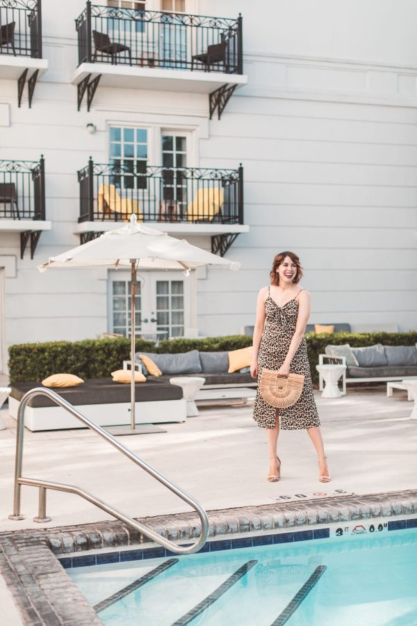 Kimpton Brice Hotel featured by top US travel blogger Greta Hollar; Image of a woman wearing a leopard print dress.