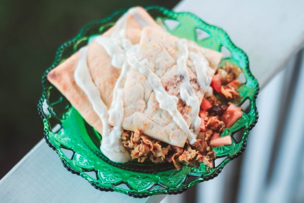 Easy Summer Turkey Pita | Greta Hollar | Easy Turkey Pita Sandwich Perfect for Summer by top US life and style blog, greta hollar: image of green glass plate, classic ranch dressing, and turkey pita sandwich.