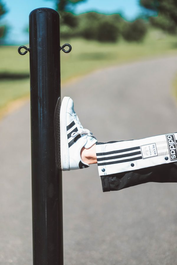 Memorial Day Outfits featured by top US fashion blogger Greta Hollar; Image of a woman wearing Adidas track pants and Adidas sneakers from Macy's.