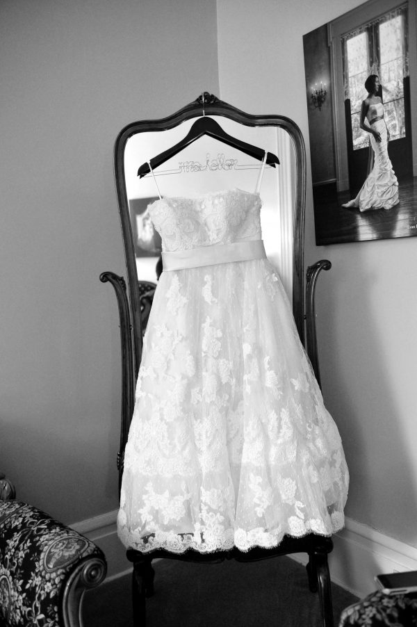 4th of July Wedding | Greta Hollar | 4th of July Wedding by popular lifestyle blogger Greta Hollar: black and white image of a The White Room tea length lace wedding dress hanging on a full body mirror.