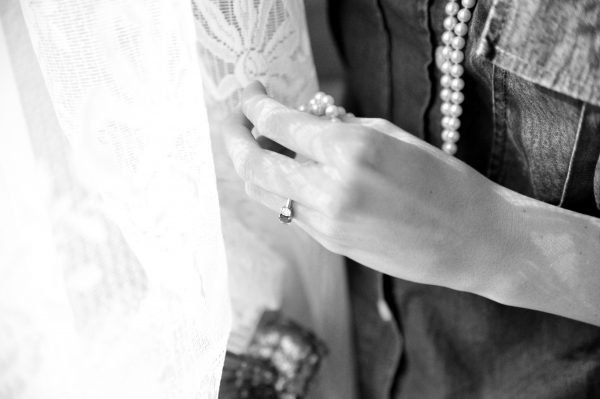 4th of July Wedding | Greta Hollar | 4th of July Wedding by popular lifestyle blogger Greta Hollar: black and white image of a hand holding a long strand of pearls.