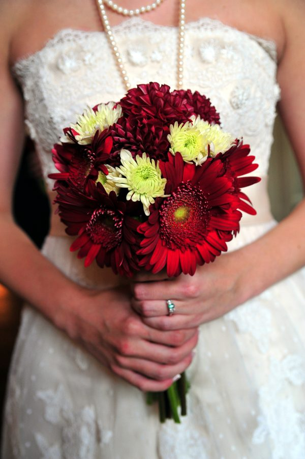 4th of July Wedding | Greta Hollar | 4th of July Wedding | Greta Hollar | 4th of July Wedding by popular lifestyle blogger Greta Hollar: close up image of a bride wearing a The White Room wedding dress and holding a red and white flower bouquet