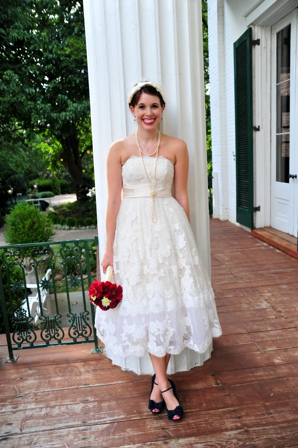 4th of July Wedding | Greta Hollar | 4th of July Wedding by popular lifestyle blogger Greta Hollar: image of a bride standing outside of a plantation house wearing a BHLDN Besotted Birdcage Veil, the White Room wedding dress, long pearl necklace black peep-toe heels from DSW and holding a red and white flower bouquet