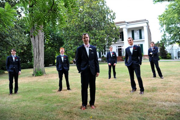 4th of July Wedding | Greta Hollar | 4th of July Wedding by popular lifestyle blogger Greta Hollar: image of a groom wearing an Indochino suit standing outside of the Riverwood Mansion in Nashville, Tennessee with his 5 groomsmen behind him.