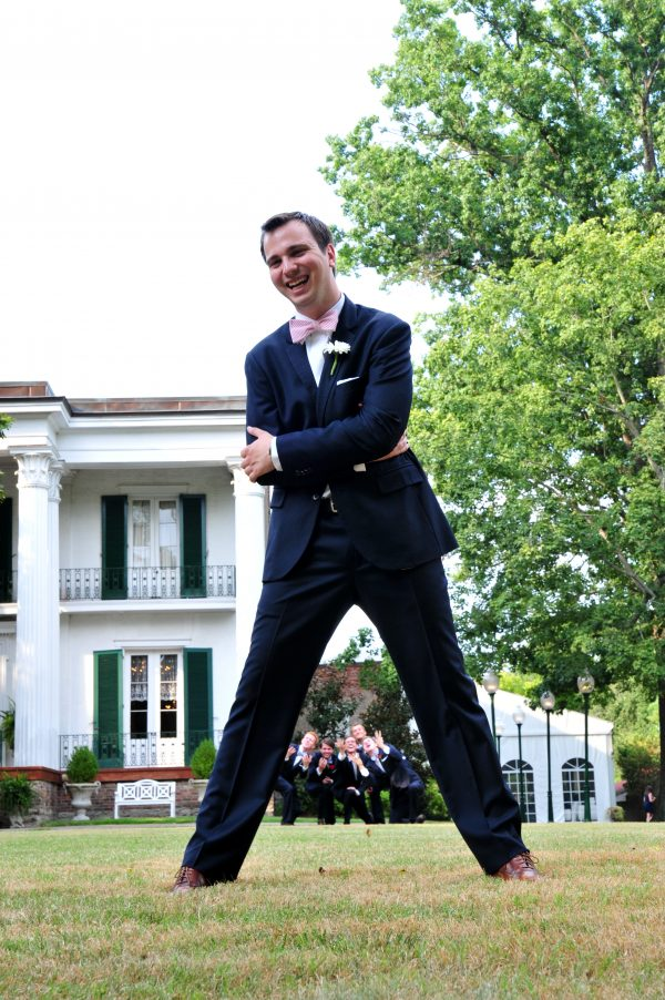 4th of July Wedding | Greta Hollar | 4th of July Wedding by popular lifestyle blogger Greta Hollar: image of a groom standing outside in front of the Riverwood Mansion in Nashville, Tennessee wearing an Indochino suit.