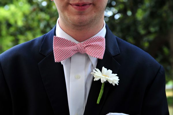 4th of July Wedding | Greta Hollar | 4th of July Wedding | Greta Hollar | 4th of July Wedding by popular lifestyle blogger Greta Hollar: closeup image of a groom wearing an indochino suit and red and white stripe bow tie.