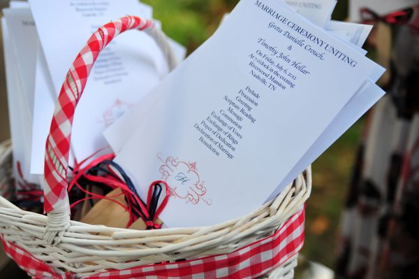 4th of July Wedding | Greta Hollar | 4th of July Wedding by popular lifestyle blogger Greta Hollar: close up image of marriage ceremony programs resting in a white wicker basket.