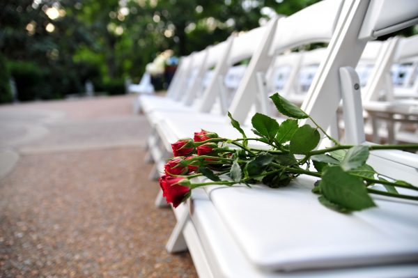 4th of July Wedding | Greta Hollar | 4th of July Wedding by popular lifestyle blogger Greta Hollar: close up image of single stem roses resting on a white folding chair.