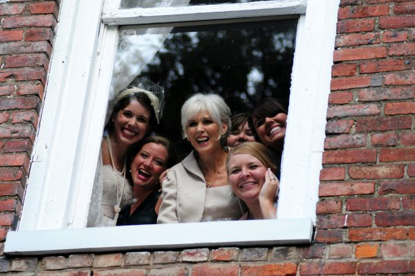 4th of July Wedding | Greta Hollar | 4th of July Wedding by popular lifestyle blogger Greta Hollar: image of a bride, bridesmaids and mother of the bride looking out of a window.