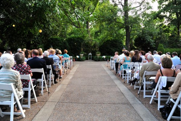 4th of July Wedding | Greta Hollar | 4th of July Wedding by popular lifestyle blogger Greta Hollar: image of wedding guests sitting outside on white folding chairs.