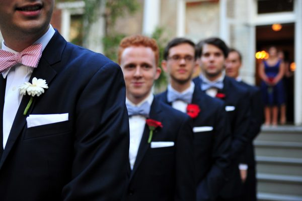 4th of July Wedding | Greta Hollar | 4th of July Wedding by popular lifestyle blogger Greta Hollar: image of a groom with his groomsmen lined up behind him.