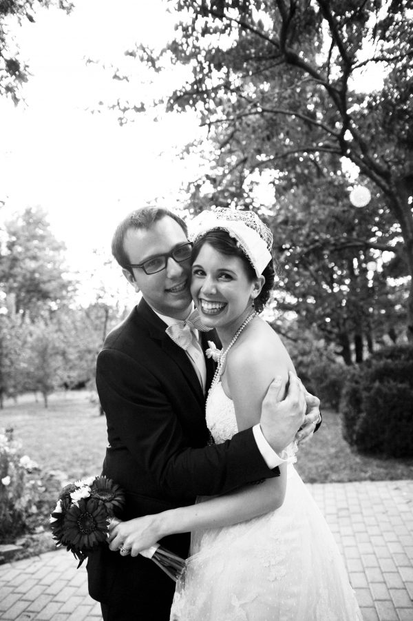 4th of July Wedding | Greta Hollar | 4th of July Wedding by popular lifestyle blogger Greta Hollar: image of a bride and groom standing together in an embrace outside. The Bride is wearing BHLDN Besotted Birdcage Veil, the White Room wedding dress, and blue peep toe heels from DSW and the groom is wearing an Indochino suit.