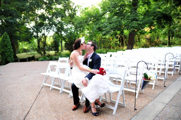 4th of July Wedding | Greta Hollar | 4th of July Wedding by popular lifestyle blogger Greta Hollar: image of a bride and groom sitting outside on a white folding chair and kissing. The Bride is wearing BHLDN Besotted Birdcage Veil, the White Room wedding dress, and blue peep toe heels from DSW and the groom is wearing an Indochino suit.