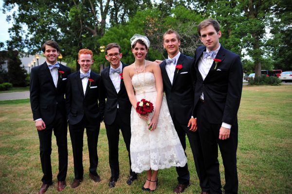4th of July Wedding | Greta Hollar |4th of July Wedding by popular lifestyle blogger Greta Hollar: image of a bride wearing a BHLDN Besotted Birdcage Veil, the White Room wedding dress, and blue peep toe heels from DSW and standing with 5 groomsmen.