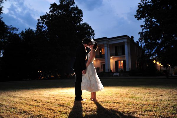 4th of July Wedding | Greta Hollar | 4th of July Wedding by popular lifestyle blogger Greta Hollar: image of a bride and groom kissing outside in front of the Riverwood Mansion in Nashville, Tennessee. The Bride is wearing BHLDN Besotted Birdcage Veil, the White Room wedding dress, and blue peep toe heels from DSW and the groom is wearing an Indochino suit.