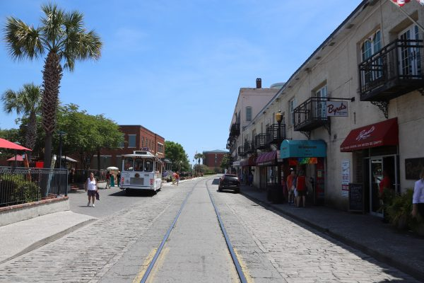 Savannah Travel Guide | Greta Hollar | he Ultimate Savannah Travel Guide by popular Nashville lifestyle blogger, Greta Hollar: image of city street with trolley track and a trolley.