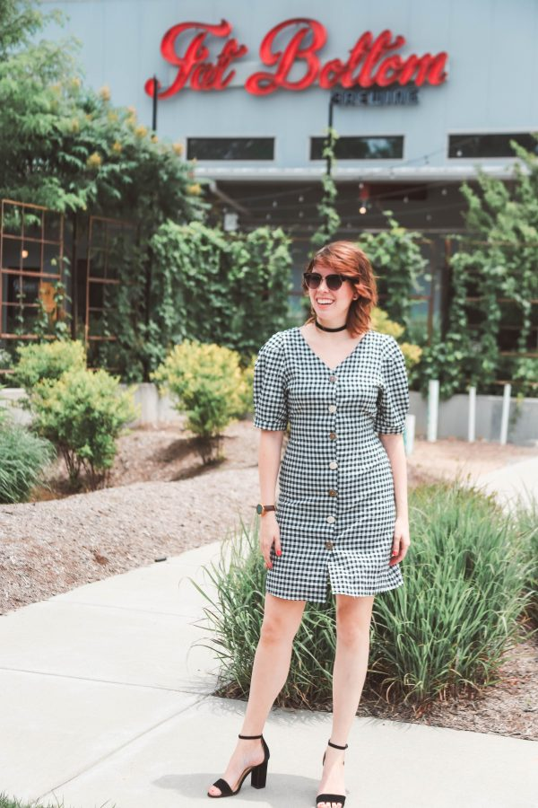 All the Breweries You Should Visit In Nashville | Greta Hollar | 14 of the Best Nashville Breweries to Visit by popular Nashville lifestyle blogger, Greta Hollar: image of a woman in a black and white gingham dress standing in front of Fat Bottom brewery in Nashville, Tennessee.