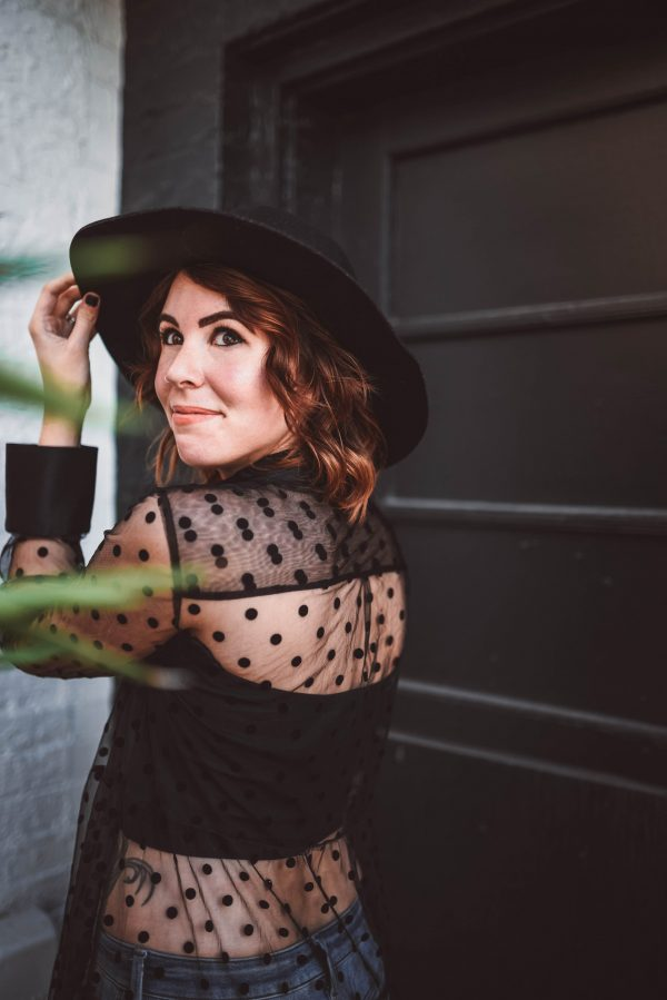 Blogging Tips on How to Get Your Blog ready for Vacation by popular Nashville fashion blogger, Greta Hollar: image of a woman standing next to a black wall and wearing a black polka dot mesh top and black felt hat.