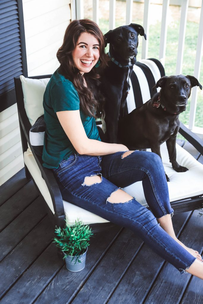 The Piece You Need for Your Front Porch | Greta Hollar | 6 Lovely Valentine's Day Gifts for Pet Lovers by popular Nashville life and style blogger, Greta Hollar: image of a woman sitting outside with her two black dogs.