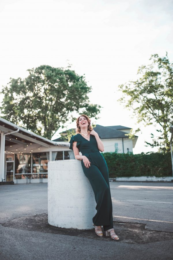 Have a Late Summer Event? Wear This Eliza J. Jumpsuit! by popular Nashville fashion blogger, Greta Hollar: image of a woman wearing a Eliza J. Flutter Sleeve Belted Satin Jumpsuit.