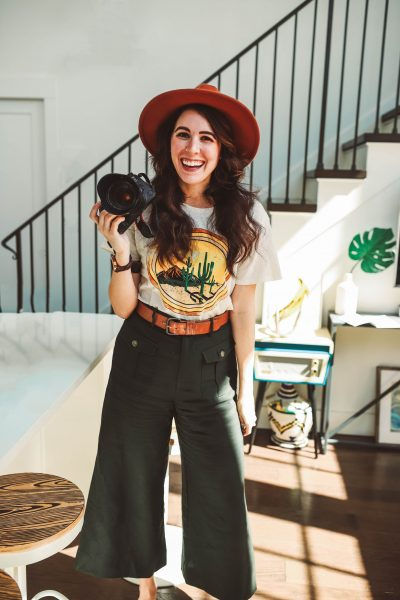 A Stay at The Waverly Nashville | Greta Hollar | A Stay at The Waverly Nashville by popular Nashville blogger, Greta Hollar: image of a woman wearing a cactus print t-shirt, felt fedora, and holding a camera inside the Waverly Nashville Hotel.