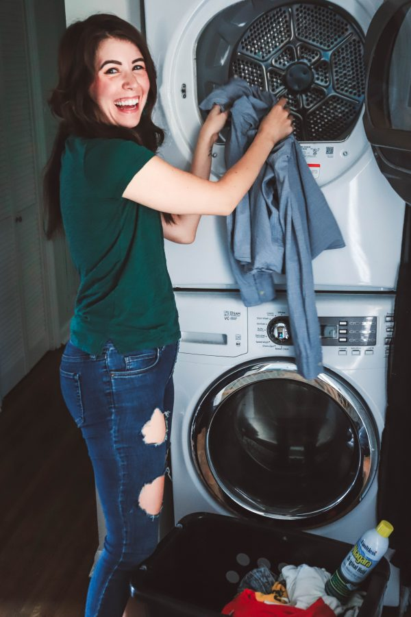 How to Get Ready for the Week on Sunday | Greta Hollar | How to Get Ready for the Week on Sunday by popular Nashville lifestyle blogger, Greta Hollar: image of a woman putting a button down shirt into the dryer.