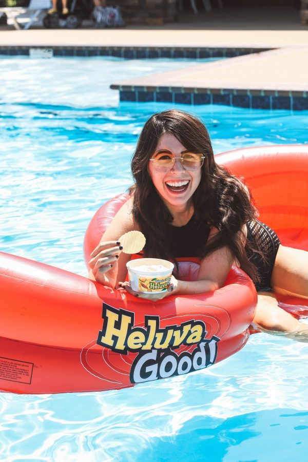 Taking a Dip with Heluva Good! Dip | Greta Hollar | Taking a Dip with Heluva Good! Dip by popular Nashville life and style blogger, Greta Hollar: image of a woman sitting in a pool floating and dipping a ruffled potato chip in a container of Heluva Good! Dip.