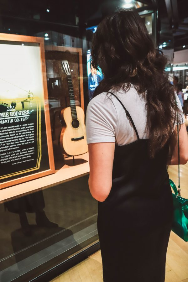 Troubadour Membership at The Country Music Hall of Fame and Museum | Greta Hollar | Troubadour Membership at The Country Music Hall of Fame and Museum in Nashville by popular Nashville blogger, Greta Hollar: image of a woman looking at a country singer's guitar at the Country Music Hall of Fame and Museum