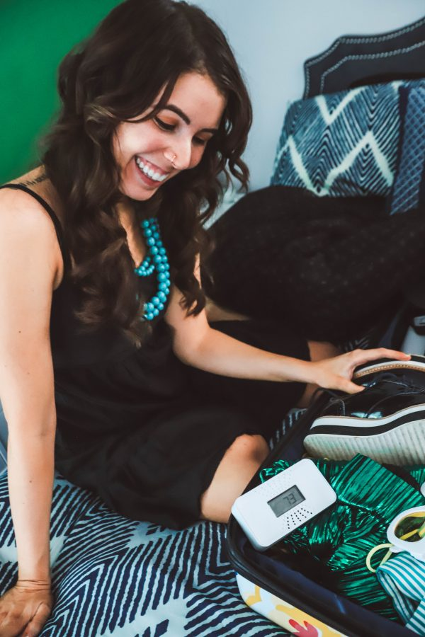 The One Thing I'm Packing for My End of Summer Vacation? My First Alert CO Alarm! | Greta Hollar | The One Thing I'm Packing for My End of Summer Vacation? My First Alert CO Alarm! by popular Nashville life and style blogger, Greta Hollar: image of a woman looking at a First Alert CO alarm in her suitcase.