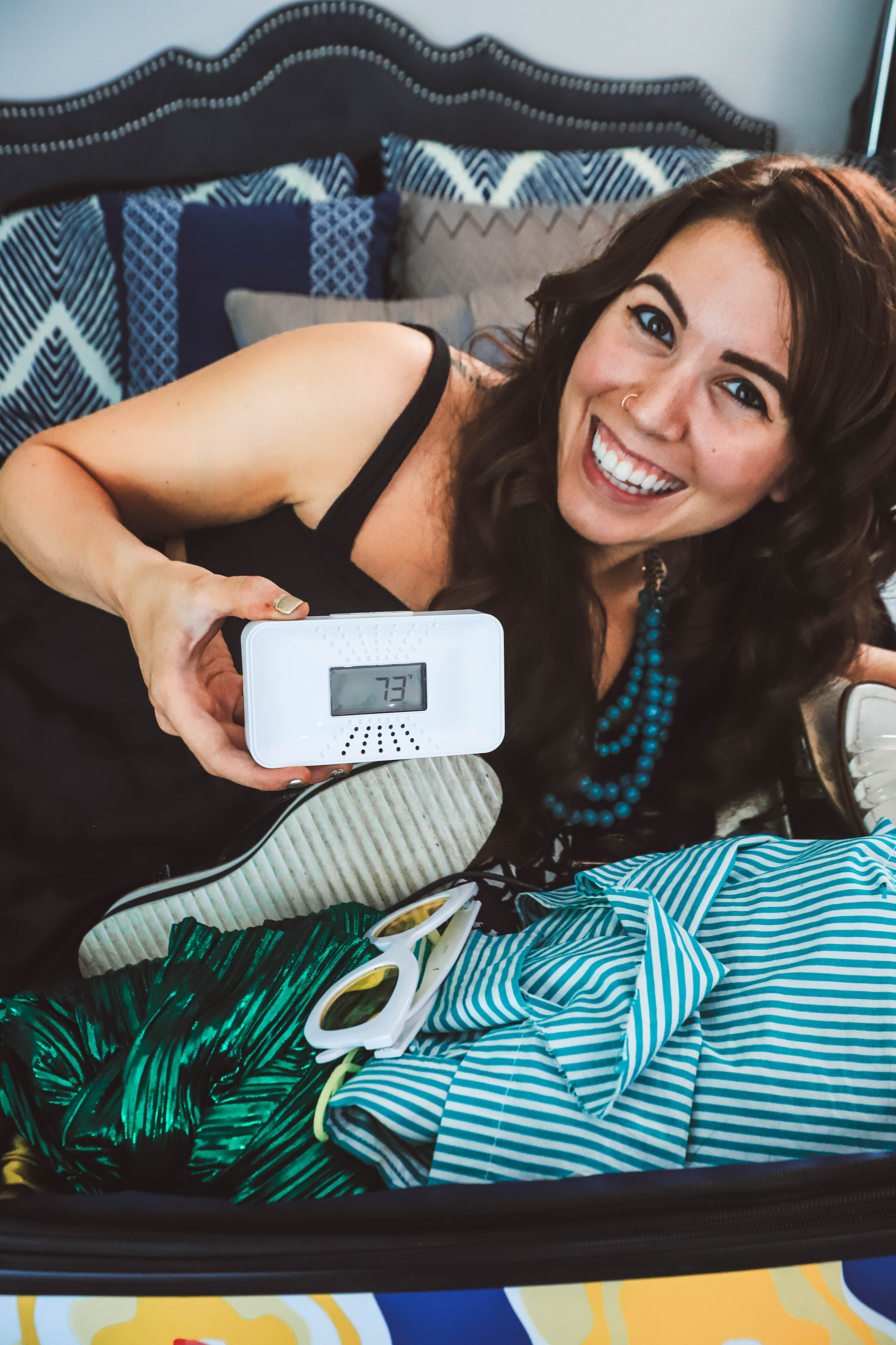 The One Thing I'm Packing for My End of Summer Vacation? My First Alert CO Alarm! by popular Nashville life and style blogger, Greta Hollar: image of a woman sitting on her bed and holding a First Alert CO alarm in her hand.