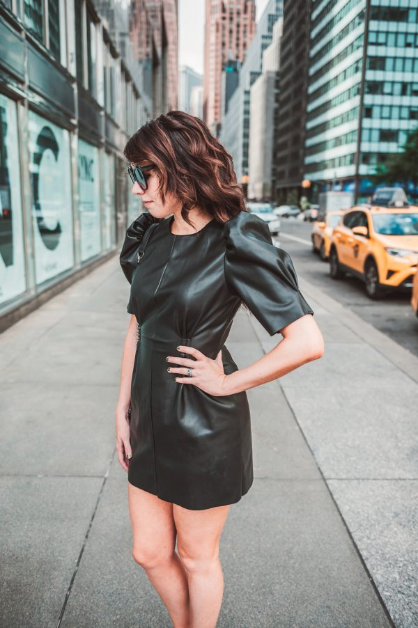 Two Ways to Style Faux Leather Pieces | Greta Hollar | Two Ways to Style Faux Leather Clothing by popular Nashville fashion blogger, Greta Hollar: image of woman outside in New York City wearing a Zara LEATHER-LOOK DRESS and Adidas sneaker.