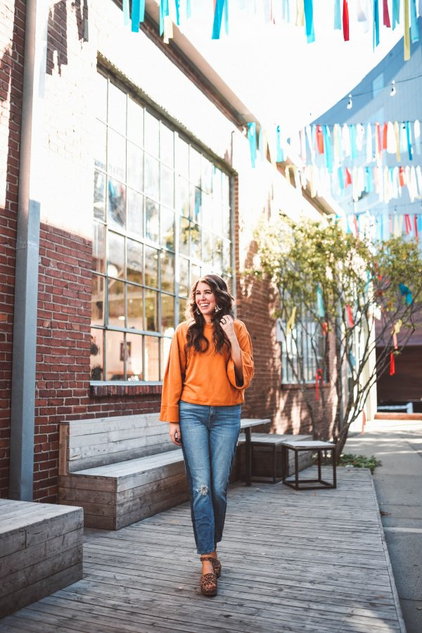 Two Pieces to Transition You From Summer to Fall | Greta Hollar | Two Pieces to Transition You From Summer to Fall by popular Nashville fashion blogger, Greta Hollar: image of woman standing outside and wearing Urban Outfitters Seychelles Calming Influence Platform Sandal, Anthropologie Thea Bell-Sleeved Sweatshirt, and The High-Rise Slim Boyjean in Barksdale Wash.