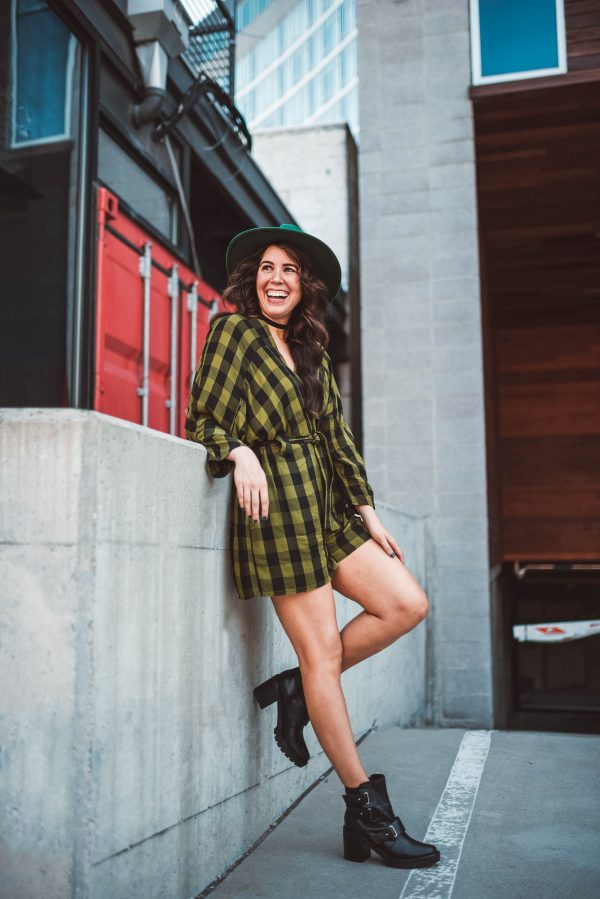 How I'm Styling Moto Boots This Fall | Greta Hollar | How I'm Styling Moto Boots This Fall by popular Nashville fashion blogger, Greta Hollar: image of a woman outside wearing a ASOS DESIGN Tall stitch detail slouchy tie waist romper in green check, Brixton Wesley Fedora, and Nordstrom Marc Fisher Dream Moto Boot.