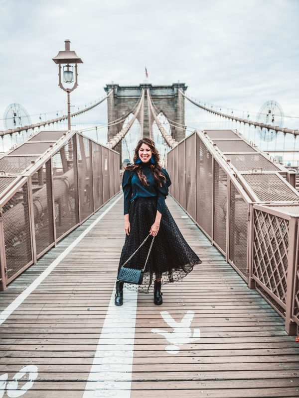 How to Get the Perfect Photo On the Brooklyn Bridge | Greta Hollar | How to Take a Picture at the Brooklyn Bridge by popular Nashville lifestyle blogger, Greta Hollar: image of a woman standing on the Brooklyn Bridge.