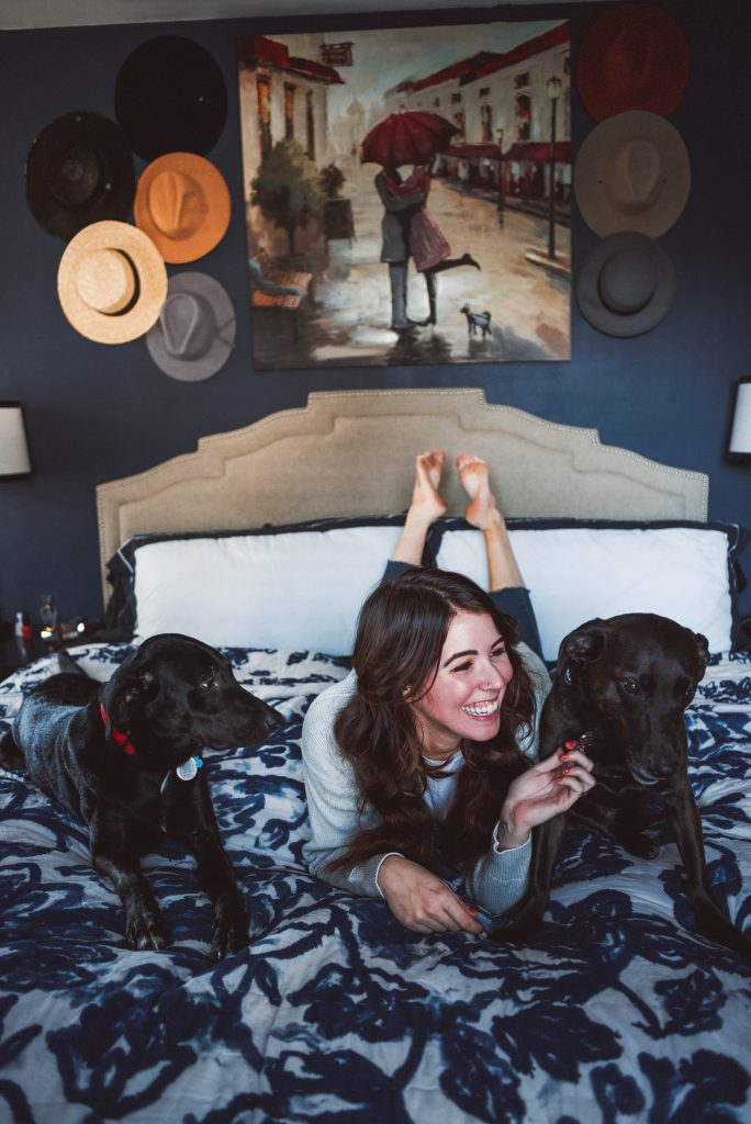 Master Bedroom Reveal | Greta Hollar | 6 Lovely Valentine's Day Gifts for Pet Lovers by popular Nashville life and style blogger, Greta Hollar: image of a woman laying on her bed with her two black dogs.