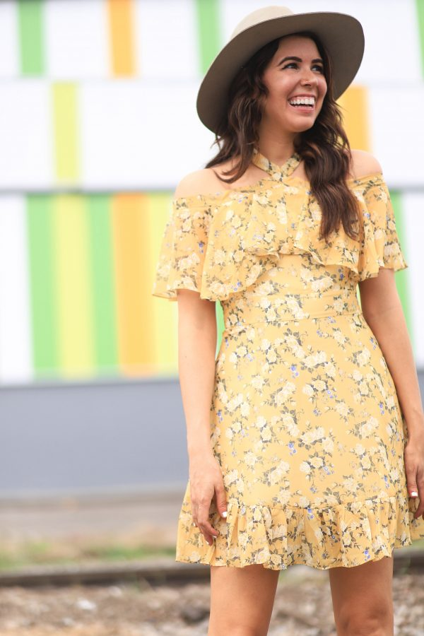 5 of My Favorite Podcasts | Greta Hollar | 5 of My Favorite Podcasts by popular Nashville lifestyle blogger, Greta Hollar: image of a woman standing outside and wearing a yellow floral print off-shoulder dress and felt hat.