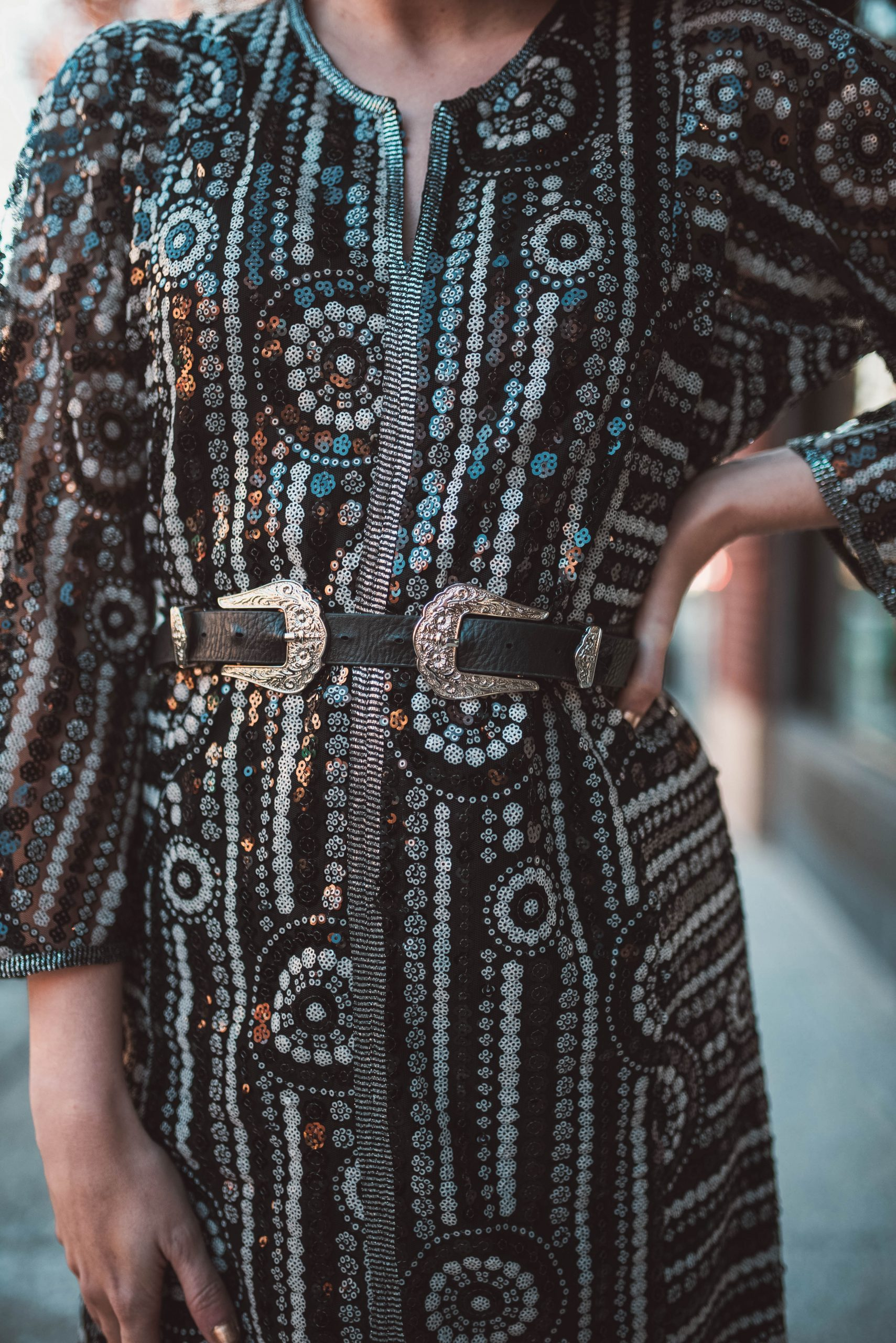 Nashville Style: How to Dress Like a Local by popular Nashville fashion blogger, Greta Hollar: image of a woman outside wearing a Free People Sequin Maxi Dress, Asos leather double buckle western waist and hip belt, Brixton hat, Marc Fisher LTD Dream Moto Boot.