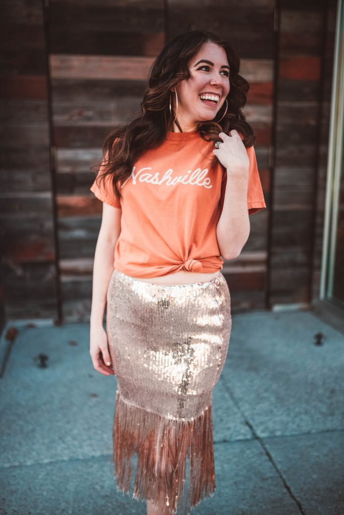 5 Cute Valentine's Day Looks that Aren't Dresses | Greta Hollar |Valentine's Day Looks by popular Nashville tall fashion blogger, Greta Hollar: image of Greta Hollar wearing a  gold sequin fringe skirt with a orange Nashville shirt.
